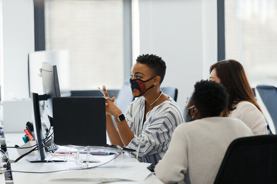 Business people in face masks working at computer in office