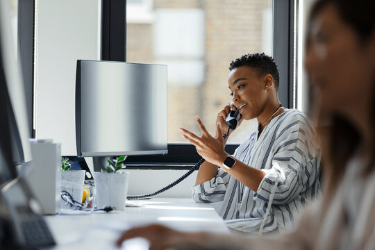 Businesswoman talking on telephone at computer in office window