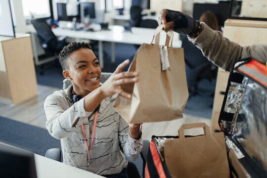 Happy businesswoman receiving lunch bag from courier in office