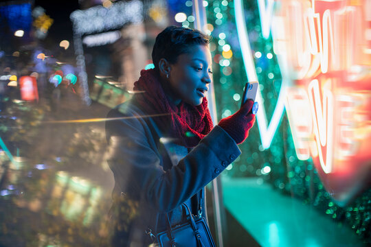 Young woman with smart phone at neon storefront sign at night