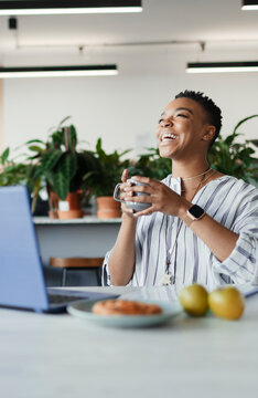 Happy businesswoman with coffee laughing at laptop in office