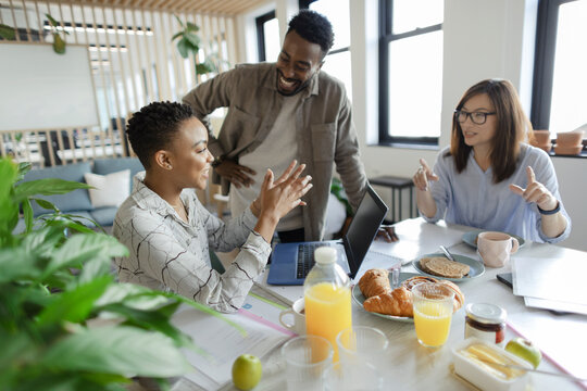 Business people talking over breakfast in office meeting