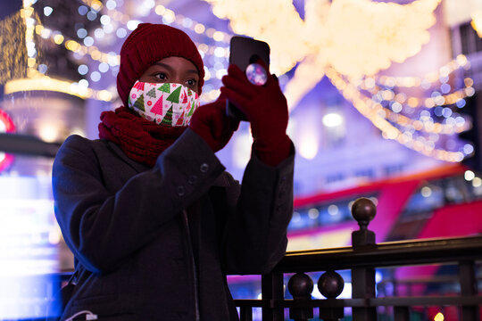 Young woman in Christmas mask taking selfie among city lights at night