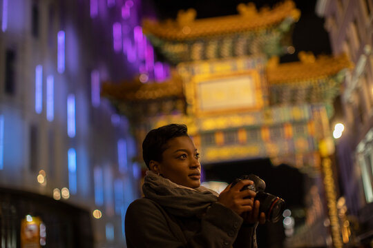 Young woman with camera below Chinatown Gate at night, London, UK