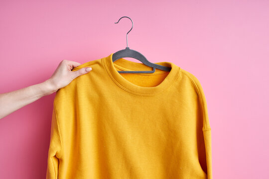 female hands holding casual clothes on hanger isolated on pink background, outfit for daily life, yellow cardigan