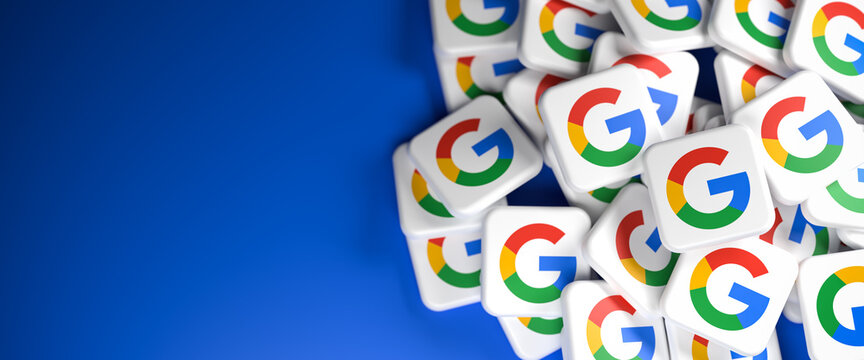 Logos of the company Google / Alphabet on a heap on a table. Copy space and selective focus. Web banner format.