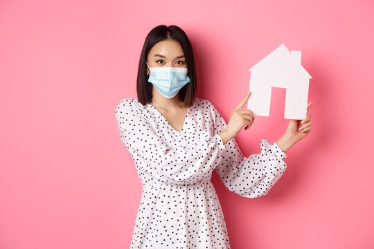 Covid-19, real estate and lifestyle concept. Cute asian woman in face mask selling houses, showing model of home and looking at camera, standing over pink background