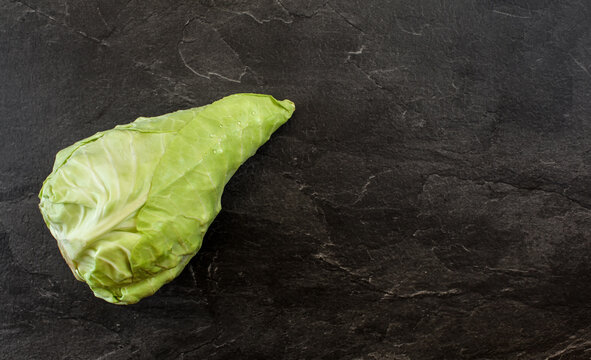 White pointed cabbage - also known as sweetheart hispi with few water drops on leaves - black table with slate like structure, under view from above, space for text right side