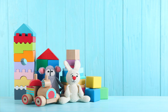 Set of different toys on light blue wooden table. Space for text