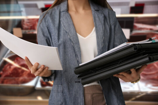 Inspector with folders and documents at wholesale market, closeup. Quality control