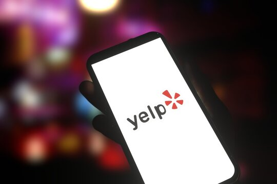 Logo of business reviewing service Yelp displayed on smartphone screen. Editorial 3d rendering.
