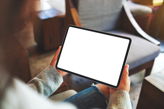 Mockup image of a woman holding digital tablet with blank white desktop screen