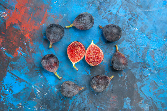 Horizontal view of full fresh black mission figs and split ones on blue background