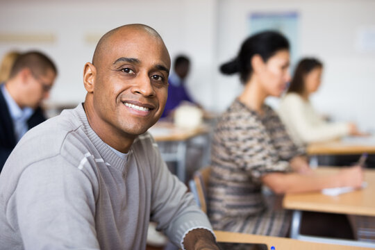 Portrait of focused young adult male studying in classroom with colleagues
