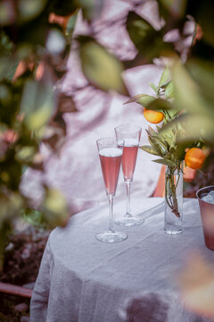 Table near the orange tree in the garden with two glasses of sparkling rose wine