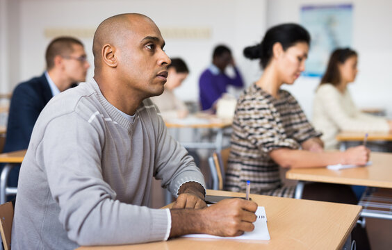Young positive man listening to lecture taking notes at adult education class