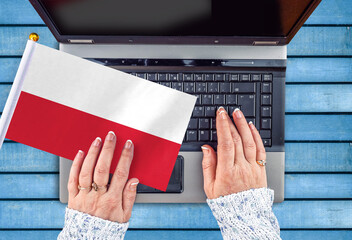 woman hands and flag of Poland on computer, laptop keyboard