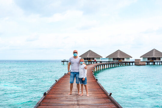 family father young man and his son wearing a protective face mask and stand on a pier near water villas in the Maldives, a concept of  travel during the covid pandemic