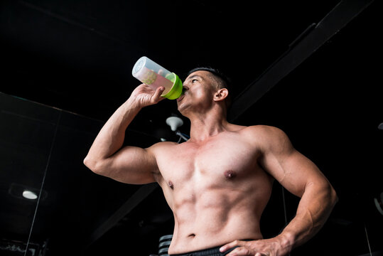 A fit asian man drinks BCAA or sports drink as a pre workout drink before an intense workout. Gym or fitness club setting.