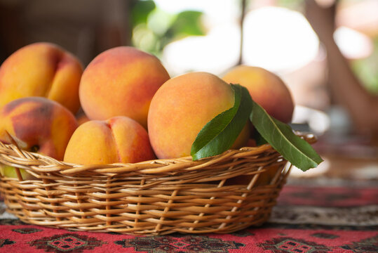 Ripe peaches fruits with leaves in basket on rustic background