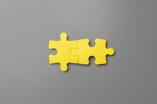 Yellow puzzle pieces on gray background close up