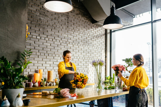 Two smiling females florists holding bouquets for orders and standing on different sides of the counter. Floristry, handmade, wedding, birthday, holiday and small business concept