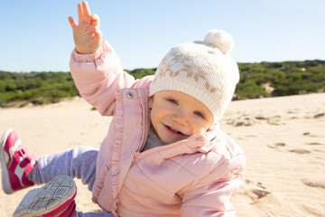 Cute baby wearing warm pink jacket and hat, sitting and rolling on sand outdoors, looking at camera and laughing. Childhood concept Wall mural