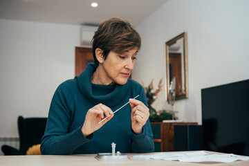 Obraz Senior woman sitting at home, studying the instructions for a self test for COVID-19 with Antigen kit on hand. Holds a nasal swab for possible infection of Coronavirus. Health services online. - fototapety do salonu