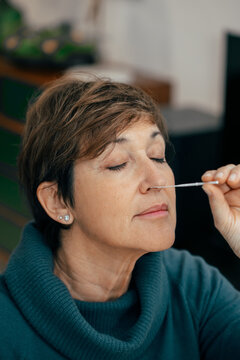 Portrait Senior woman doing a self test for COVID-19 at home with Antigen kit. Introducing nasal swab test for possible infection of Coronavirus. Medicine and health-related services online.