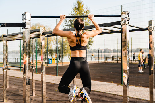 Fit strong young female athlete doing pull-ups on sporting ground