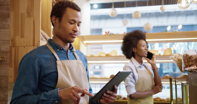 Side view. Close up of handsome young African American man worker in bakery typing and browsing on tablet while female coworker speaking on cellphone at work. Business concept. Entrepreneurs working