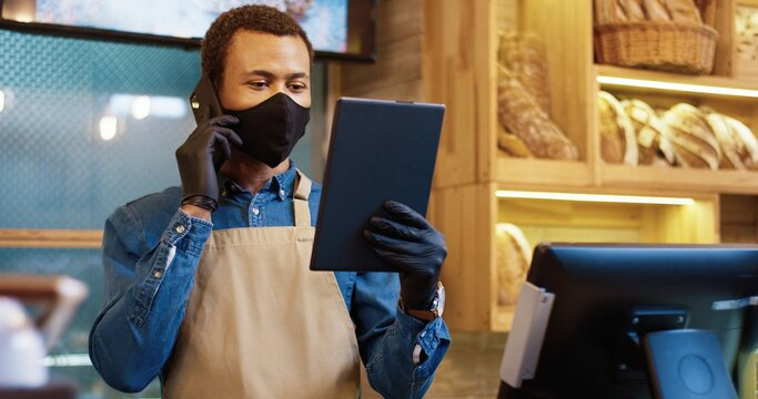 Close up portrait of happy young African American male seller in face mask and gloves using tablet device and speaking on smartphone at workplace in small own bakery. Bakehouse concept