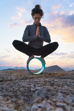 Low angle full body of focused young female sitting in Malasana pose on yoga wheel during outdoor practice in mountains at sunset