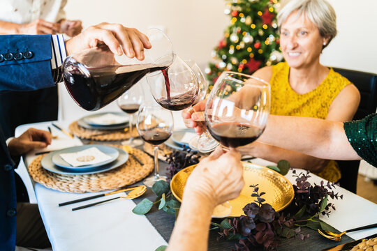 Cheerful friends and family members gathering together at table and holding glasses with red wine during Christmas dinner
