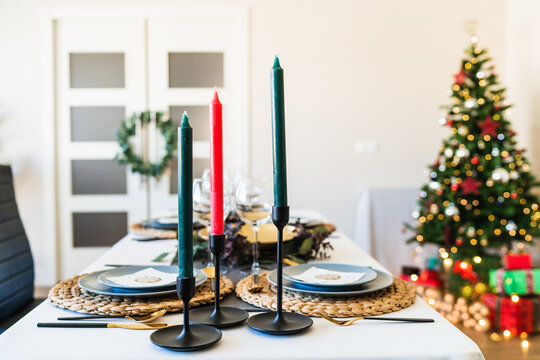 Festive table setting with candles located near fancy Christmas tree with shiny garlands in spacious living room before family gathering