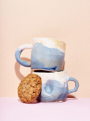 Still life of handmade ceramic mugs on bright studio background with delicious cookie