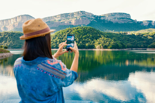 Back view of anonymous young female traveler in stylish clothing and hat taking picture with mobile phone while standing near mountain lake during summer holidays
