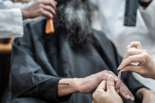 Crop female master doing manicure to male customer while barbers taking care of hair and beard in modern grooming salon