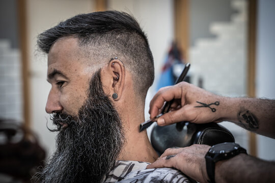 Side view of crop tattooed barber with razor finishing haircut of mature brutal bearded male consumer in barbershop