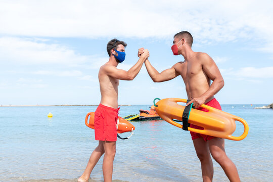 Happy young male lifeguards in shorts and masks with torpedo rescue buoy shaking hands on ocean coast while looking at each other
