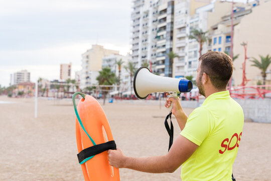 Back view of unrecognizable male lifeguard with safety buoy talking in megaphone while standing on sandy beach