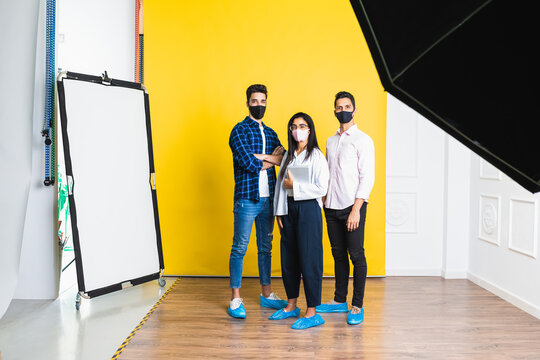 Young positive colleagues in trendy apparel and shoe covers standing with crossed arms on floor while looking at camera