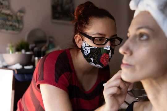 Professional makeup artist in face mask using brush while applying foundation cream on calm female customer forehead sitting in salon