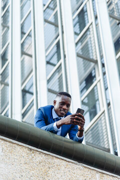 low angle of confident respectable African American businessman in formal outfit leaning on street against contemporary buildings in modern downtown with smartphone