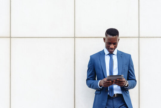 confident respectable African American businessman in formal outfit leaning on street against contemporary wall in modern downtown with smartphone