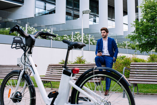 Handsome businessman in elegant clothes sitting on wooden bench while speaking on mobile phone with earbuds near electric bike in town