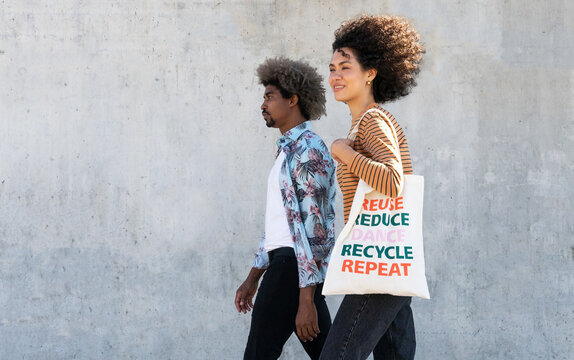 Side view of young stylish black man and woman with reusable bag walking together on street on sunny day