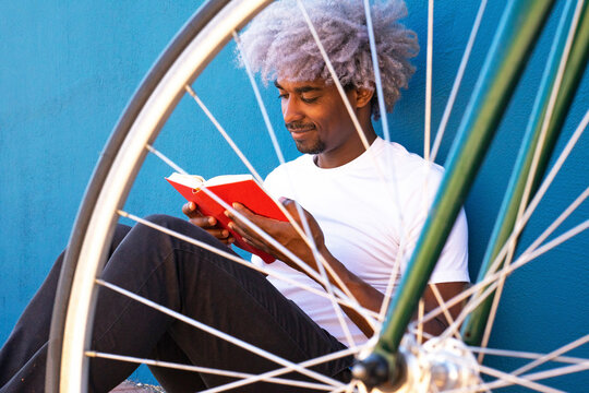Black and afro man reading a book next to his bicycle. Concept of black man reading a book.