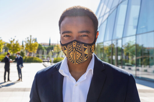 Happy young African American male entrepreneur with mask in classy suit standing on street neat contemporary business building and looking at camera