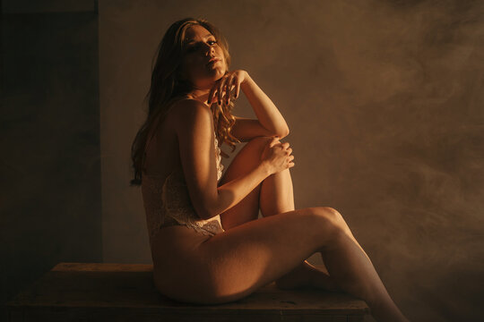 Side view of tranquil female in bodysuit sitting on wooden table and embracing knees while enjoying sunlight looking at camera